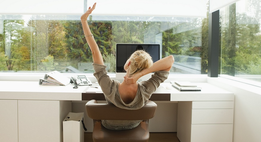 Young woman stretching at desk of office at home